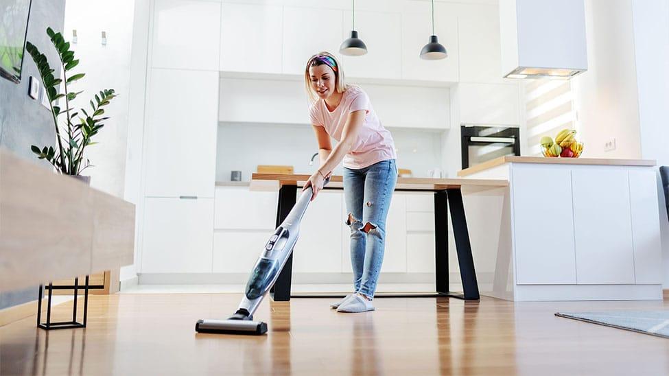 Frau putzt mit Staubsauger mit Wischfunktion in Küche