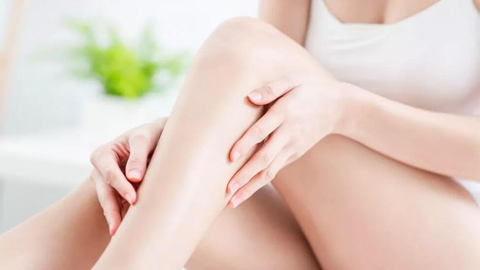 Frau trägt Feuchtigkeitscreme auf Beine auf