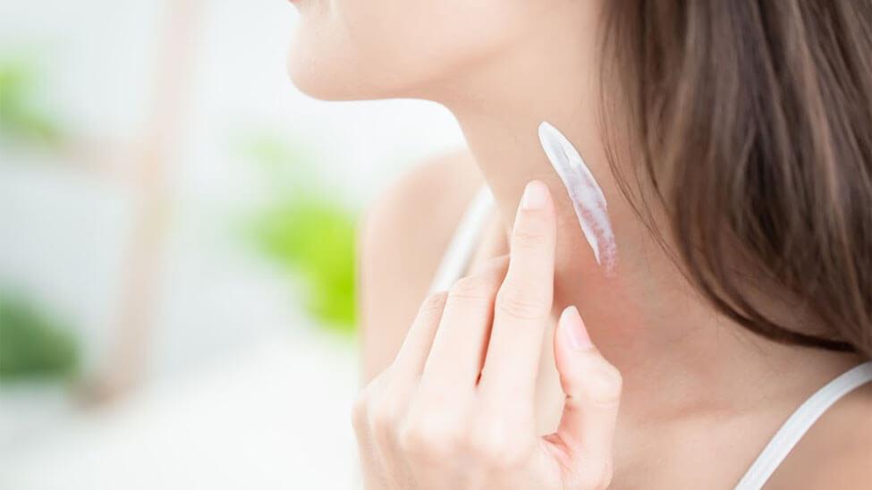 Frau trägt Feuchtigkeitscreme auf Hals auf