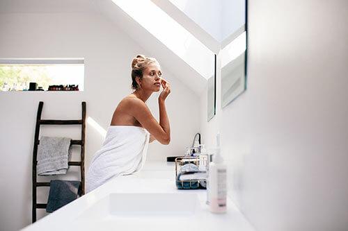 Frau trägt Feuchtigkeitscreme in Badezimmer auf