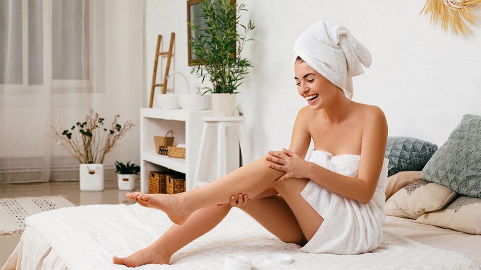 Frau trägt Feuchtigkeitscreme nach Bad auf