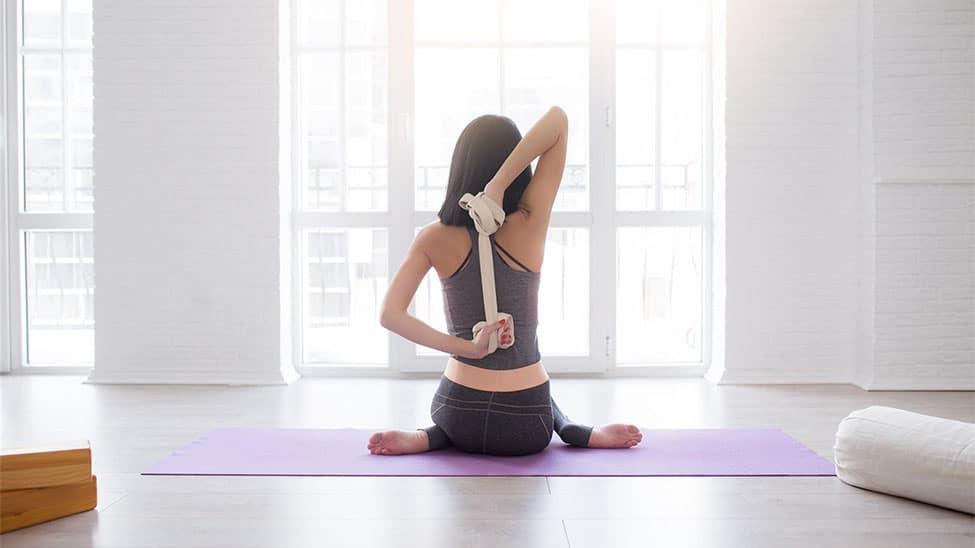 Frau trainiert zuhause mit Yogagurt am Fenster