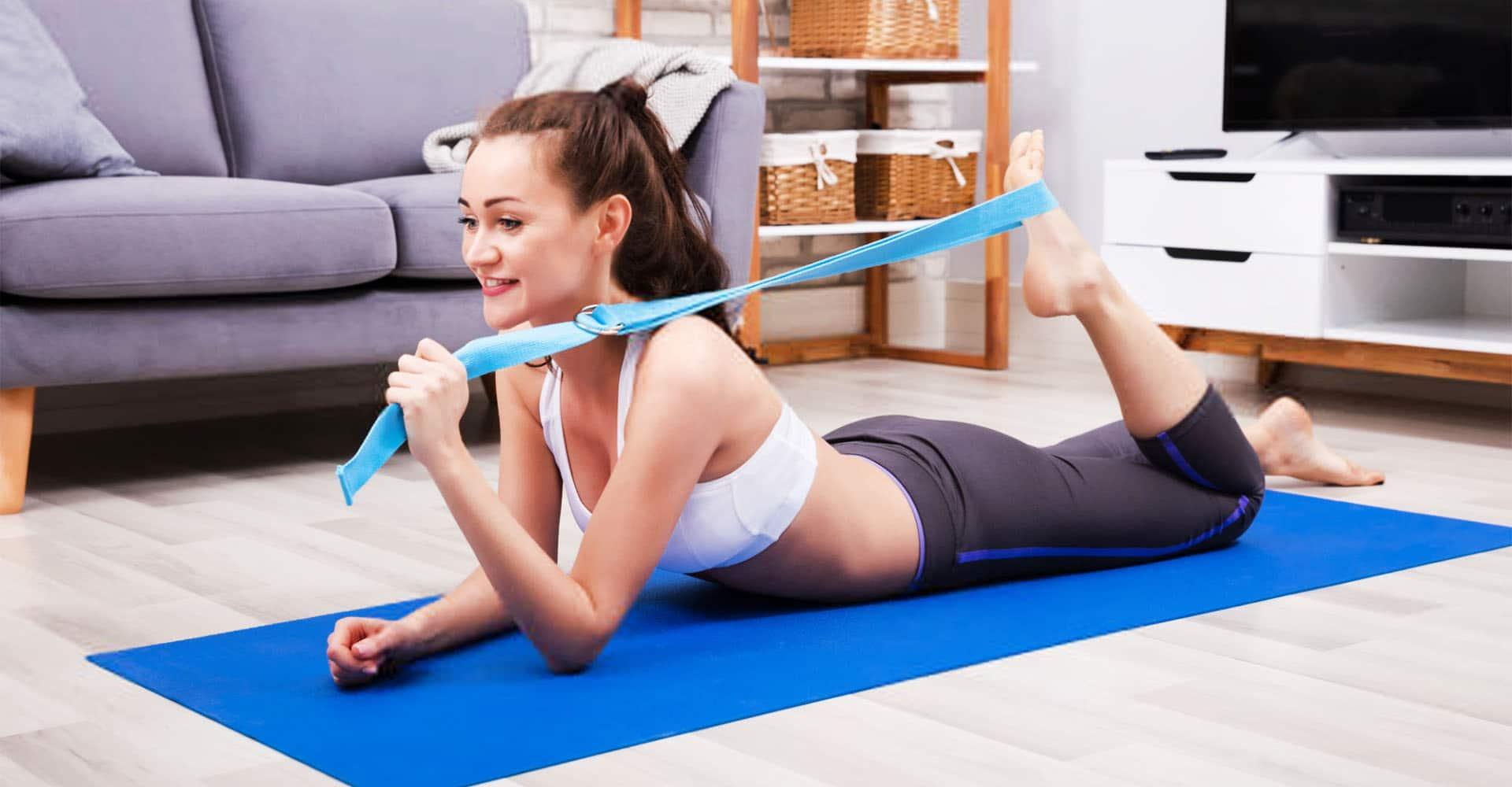 Frau trainiert zuhause mit Yogagurt
