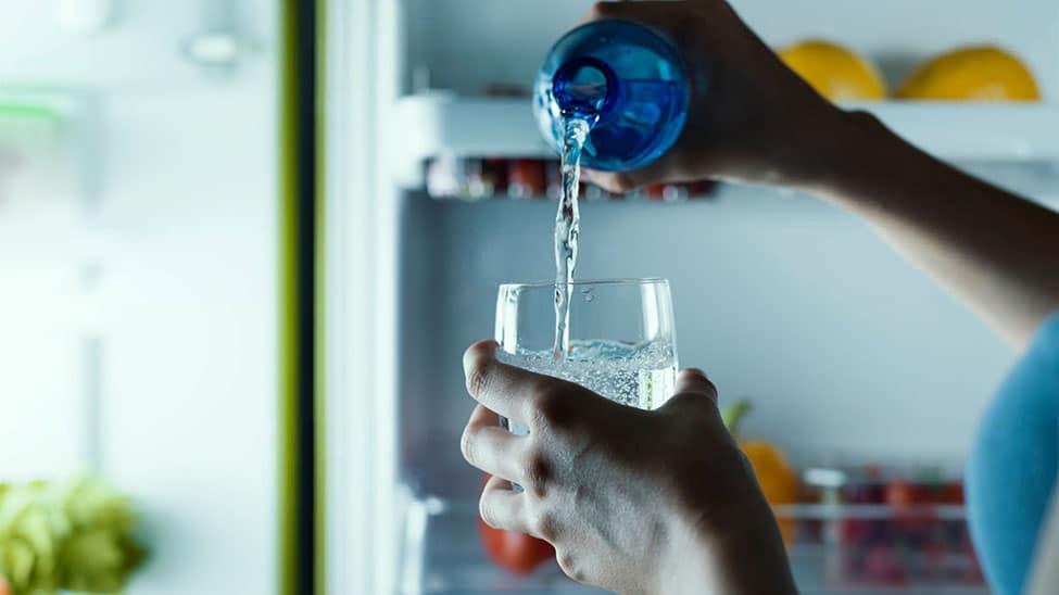 Frau trinkt Wasser aus Wassersprudler mit Glasflasche
