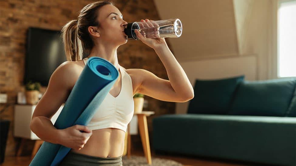 Frau trinkt aus Trinkflasche nach Sport zuhause