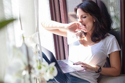 Müde Frau zuhause am Fenster mit Laptop