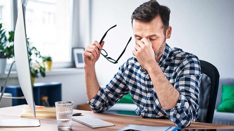 Müder Mann zuhause im Home Office