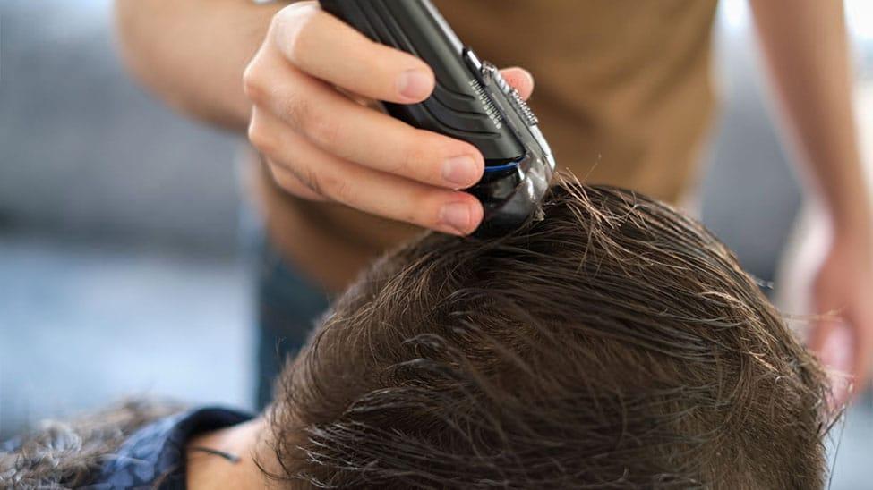 Mann bekommt Haarschnitt mit Haarschneider