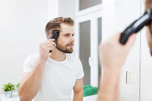 Mann mit Haarschneider im Bad