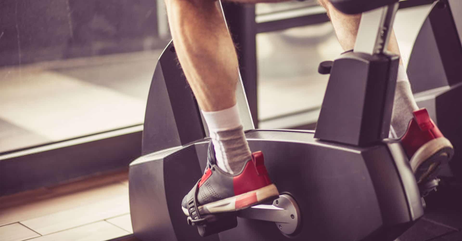 Mann trainiert auf Ergometer mit Trainingsplan