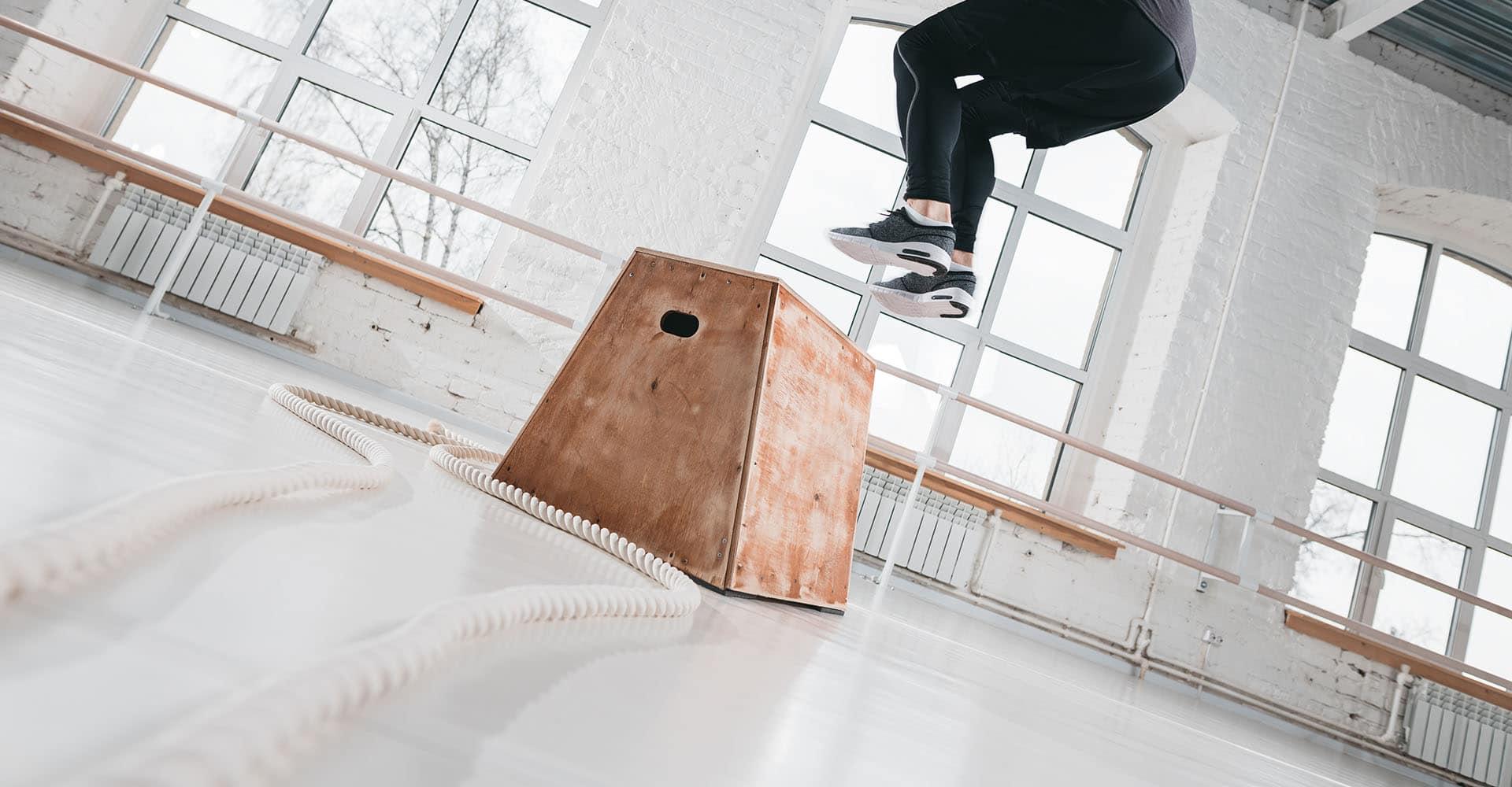 Mann trainiert zuhause mit Sprungbox