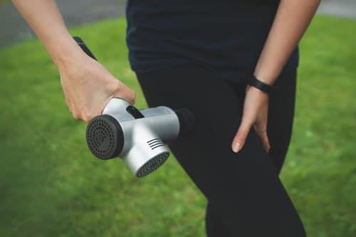 Frau nutzt Massagepistole an Bein