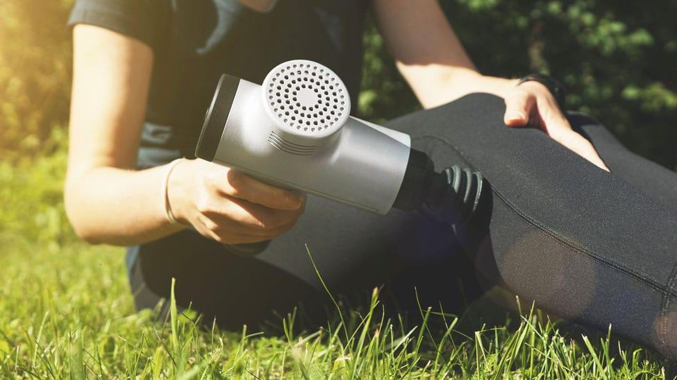 Frau nutzt Massagepistole an Knie
