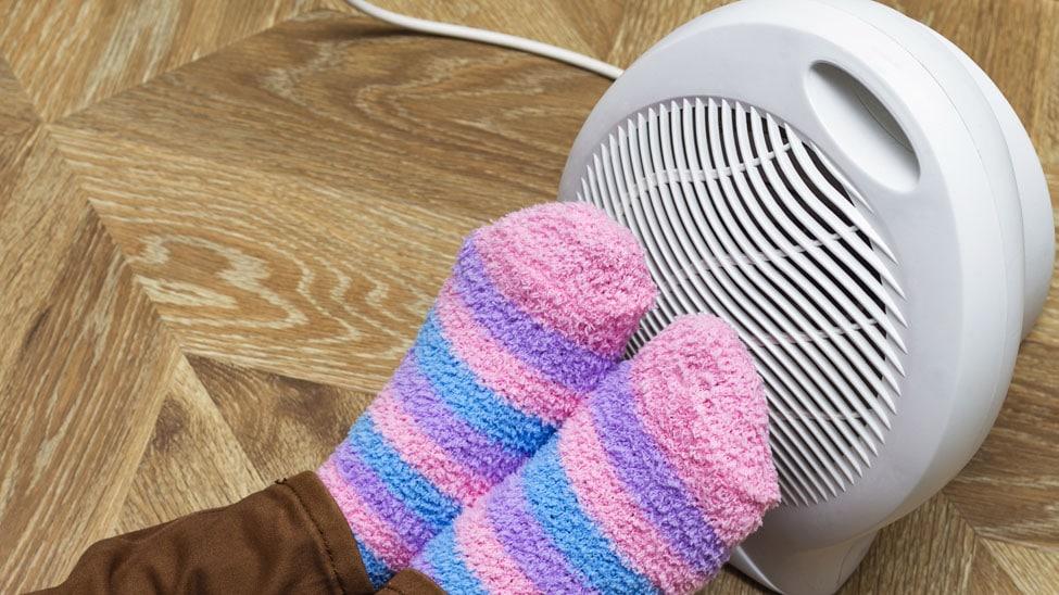 Frau wärmt Füße an Heizlüfter