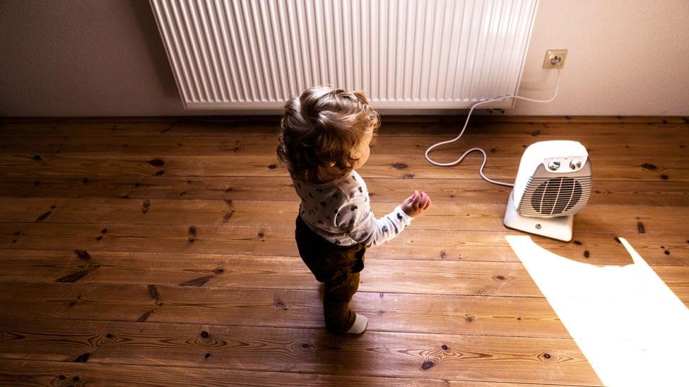Kind vor Heizlüfter