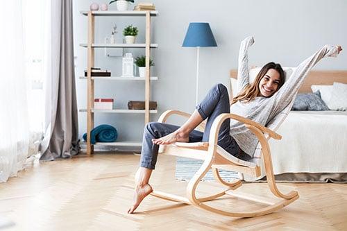 Frau entspannt sich in Sessel im Schlafzimmer