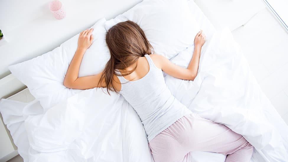 Bauchschläferin liegt im Pyjama auf Matratze
