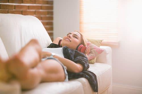 Frau auf Sofa mit Schlaf-Kopfhörer