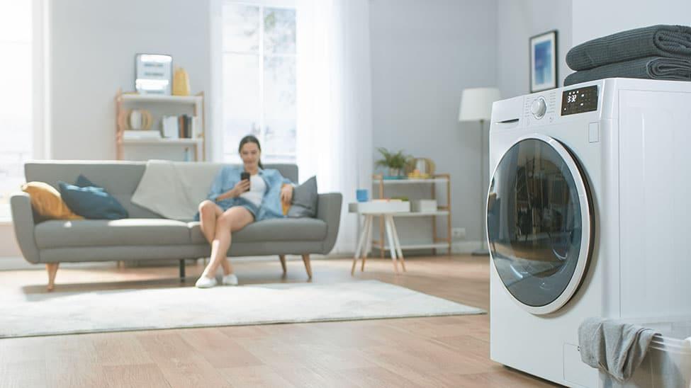 Frau bedient Waschmaschine mit Trockner über Smartphone