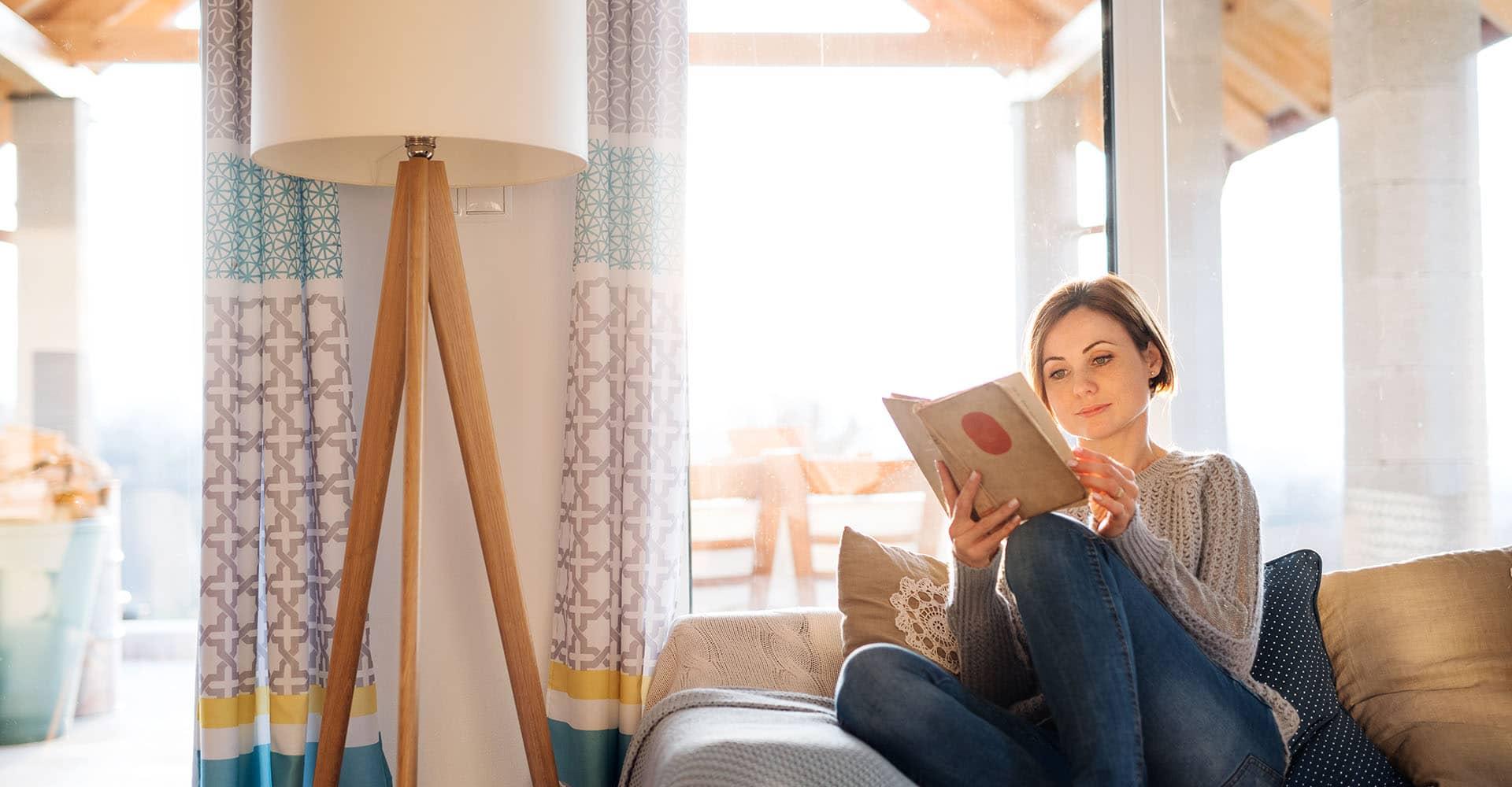 Frau liest mit Leselampe