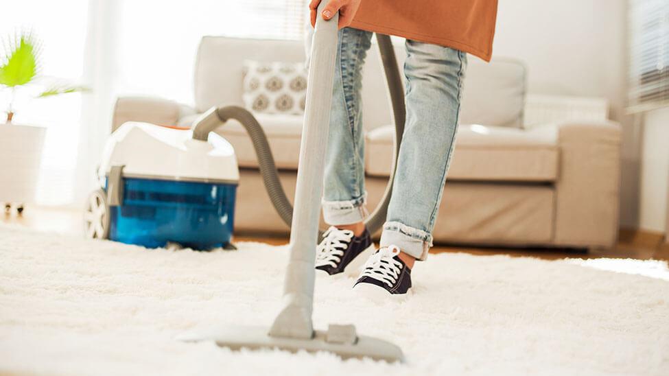 Frau macht sauber mit Teppichreiniger
