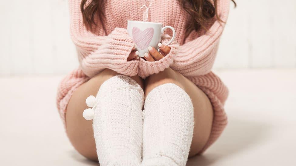 Frau mit Kuschelsocken und Tasse Tee