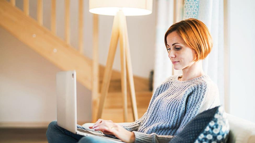 Frau mit Laptop neben Leselampe
