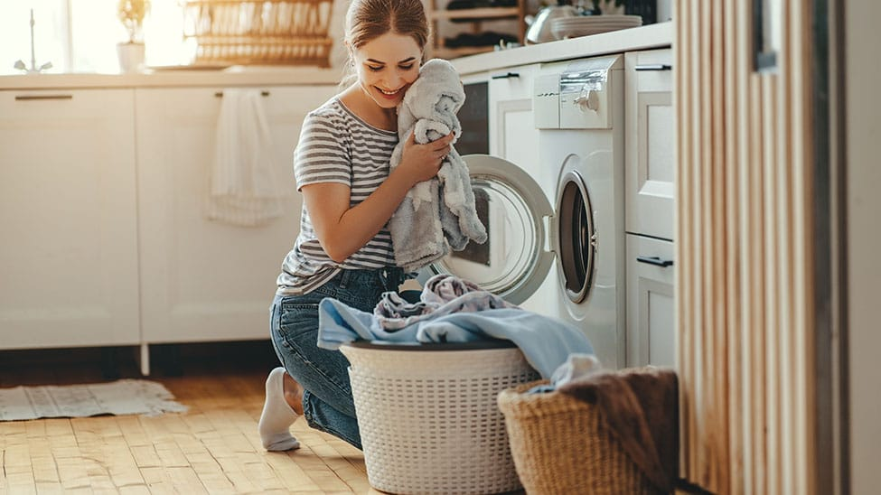 Frau nimmt Wäsche aus Trockner
