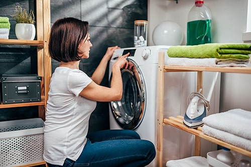Frau nutzt Waschmaschine mit Trockner
