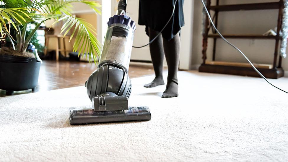 Frau nutzt großen Teppichreiniger für ihren Teppich