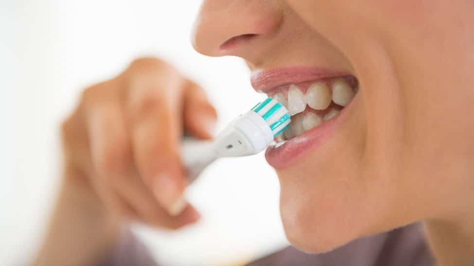 Frau putzt sich Zähne mit elektrischer Schallzahnbürste