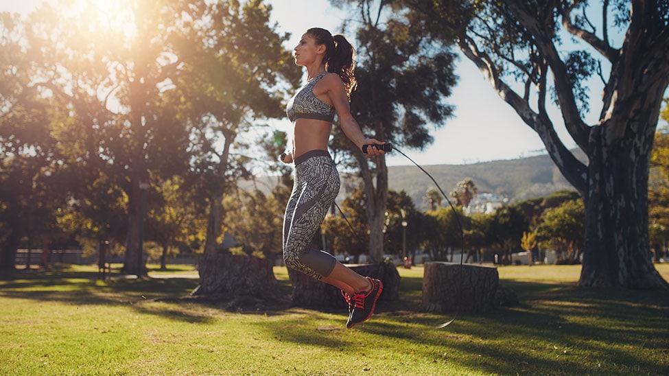 Frau springt mit Springseil draußen