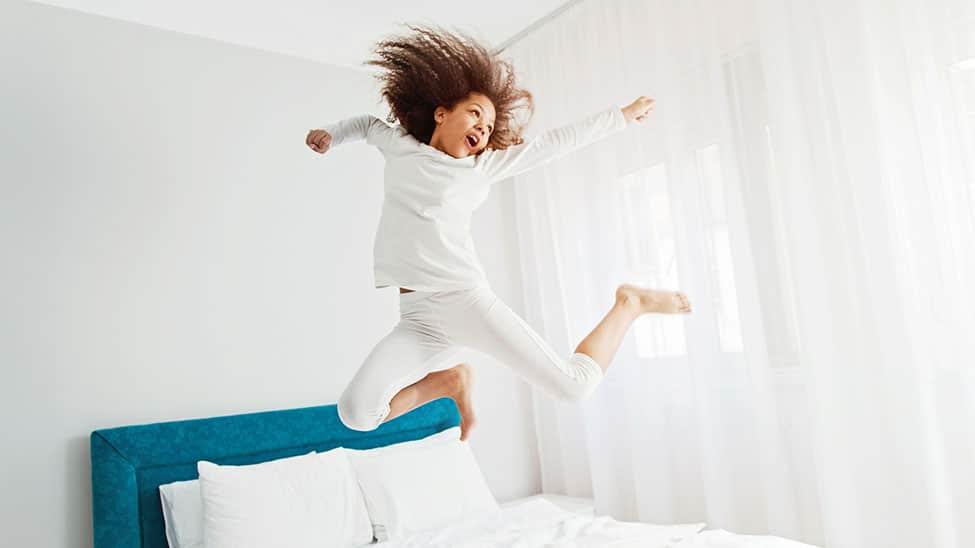 Mädchen springt auf Luftbett im Schlafzimmer