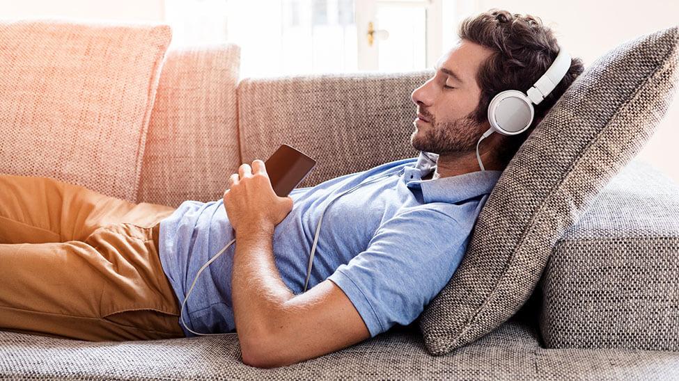 Mann auf Sofa mit Schlaf-Kopfhörer