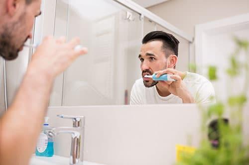Mann putzt sich Zähne mit elektrischer Schallzahnbürste