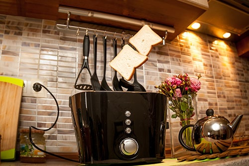 Toastbrot springt aus schwarzem Toaster