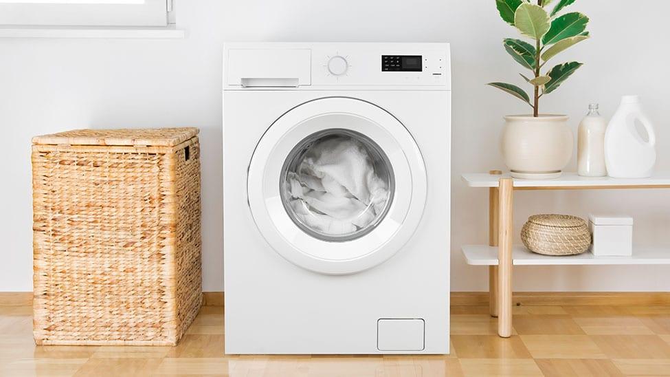 Waschmaschine im Betrieb neben Wäschekorb