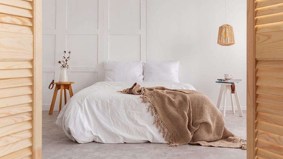 Creme-Wolldecke auf weißem Bett im Schlafzimmer