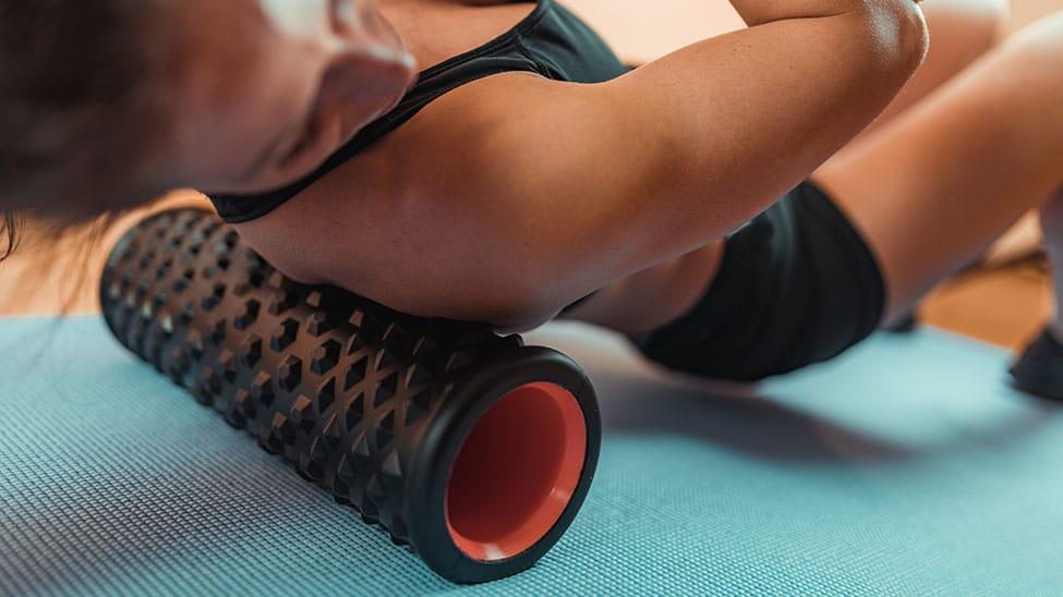 Frau bearbeitet Schulter mit Faszien Massagegerät