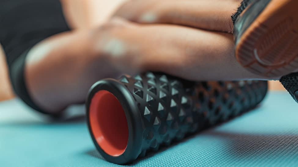 Frau bearbeitet unteren Oberschenkel mit Faszien Massagegerät