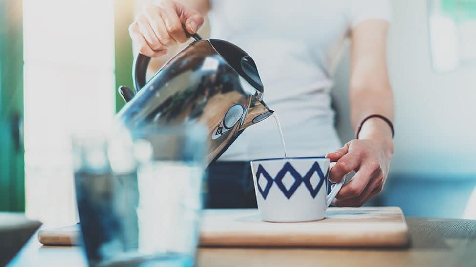 Frau gießt Wasser aus Wasserkocher ein