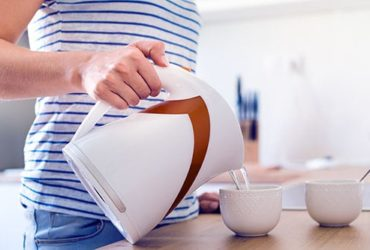 Frau macht mit Wasserkocher Tee