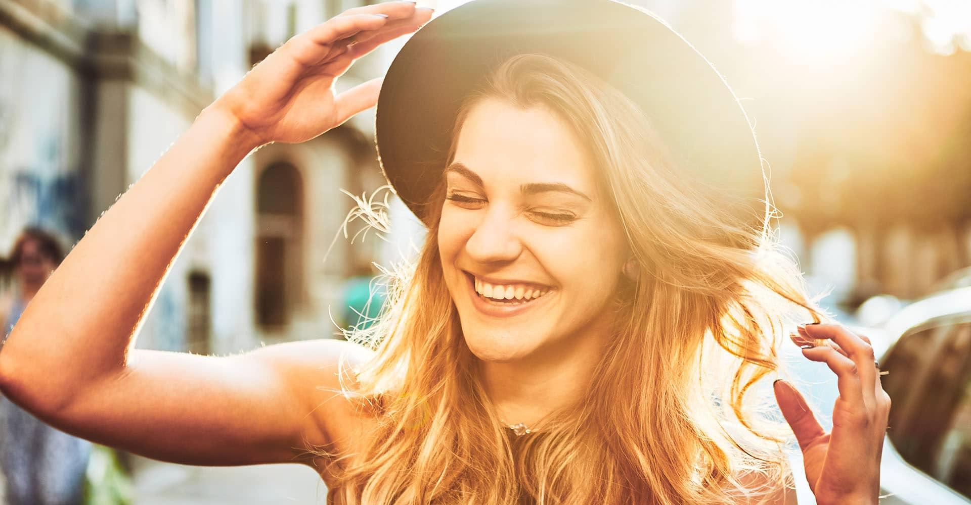 Frau mit gesunden Haaren und Hut lacht