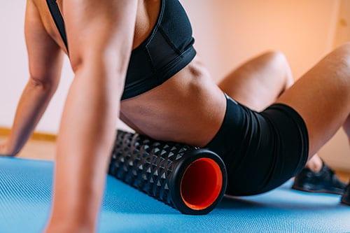 Frau nutzt Faszien Massagegerät für unteren Rücken