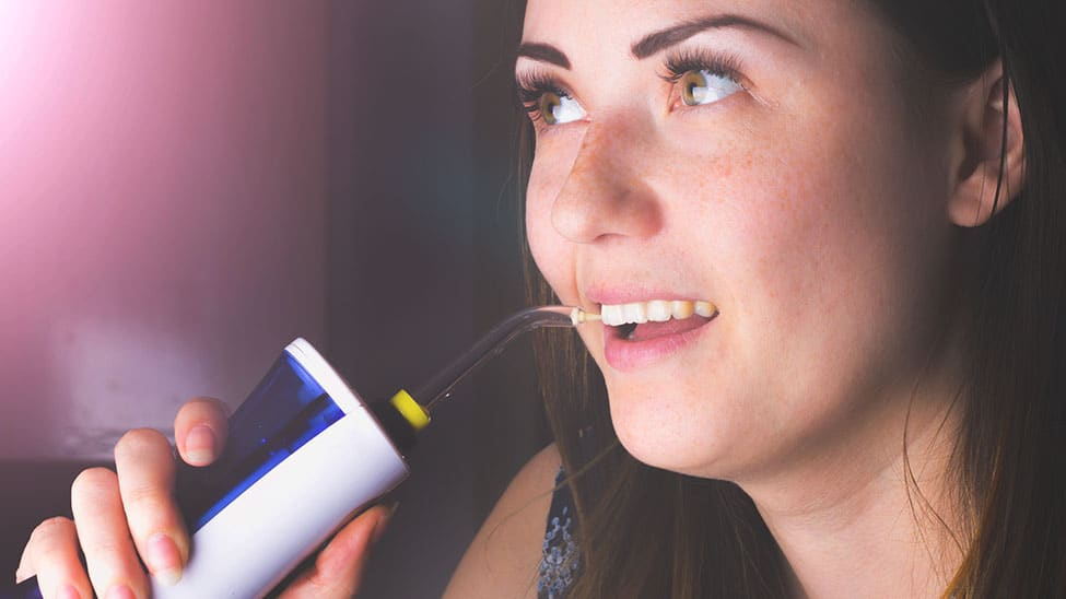 Frau nutzt Munddusche zur Reinigung