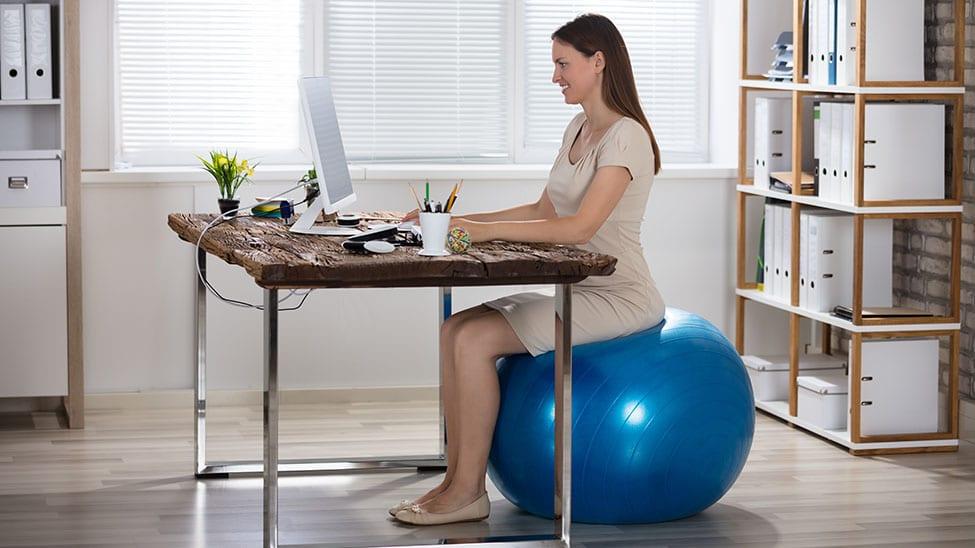 Frau sitzt im Home Office auf Gymnastikball