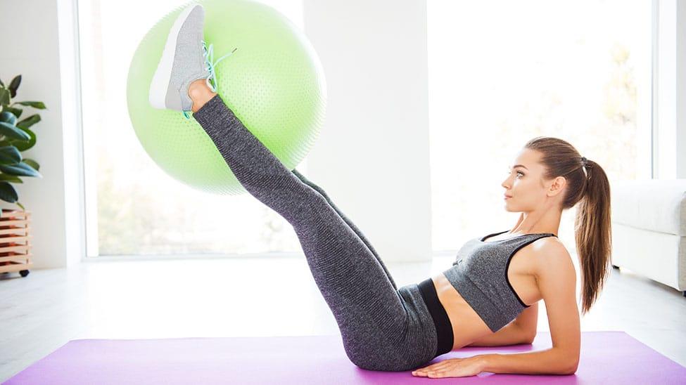 Frau trainiert auf Matte mit Gymnastikball
