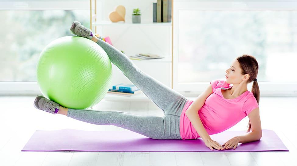 Frau trainiert auf Matte seitlich mit Gymnastikball