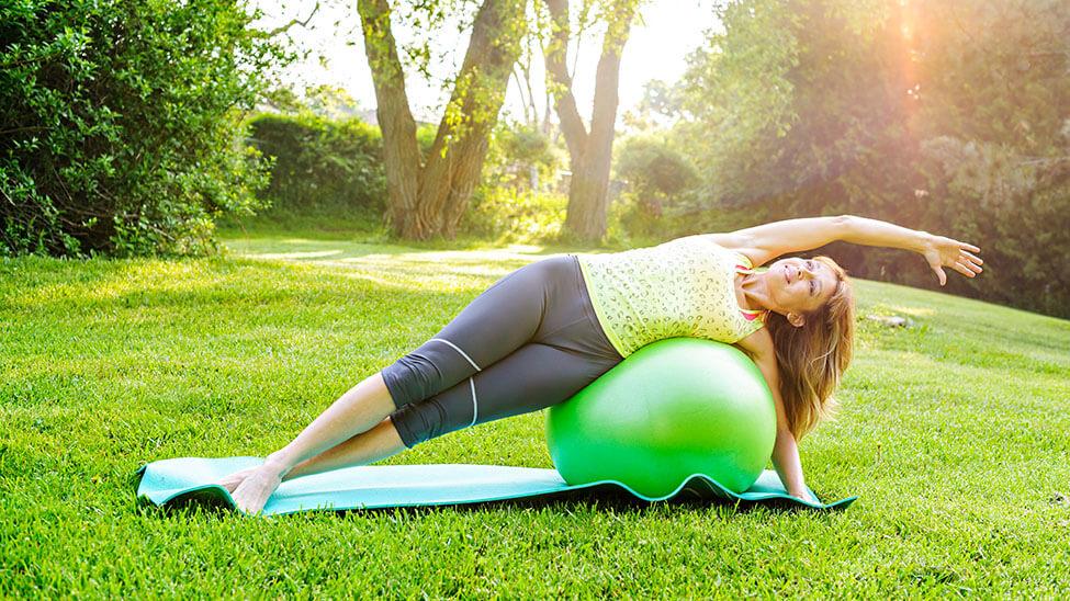 Frau trainiert draußen mit Gymnastikball