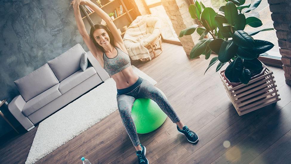 Frau trainiert in Wohnzimmer mit Gymnastikball